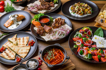 Assorted foodset on table. Kebab of pork, salmon grill, borscht, greek salad, rack of labm, fried potatoes with mushrooms.