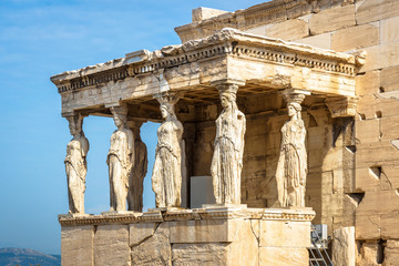 Fototapete - Erechtheion temple with Caryatid Porch on the old Acropolis, Athens, Greece. It is a famous landmark of Athens. Scenic view of Ancient Greek ruins. Beautiful antique Caryatids in the Athens center.
