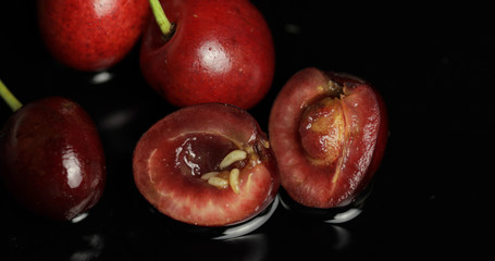 Fruit worms in rotten cherry, black background. Larva of cherry flies. Closeup