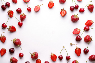 Creative berry layout made of seasonal summer fruits. Healthy food concept. Cherries and fresh juicy strawberries on white background, copy space Fototapete