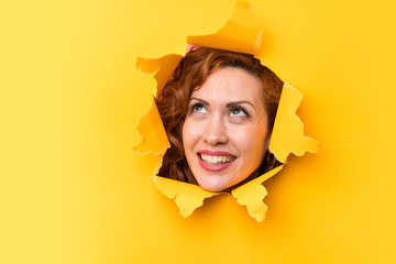 Happy Redhead woman through a hole paper