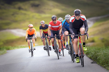 Cyclists out racing along country lanes in the mountains in the United Kingdom. Fototapete
