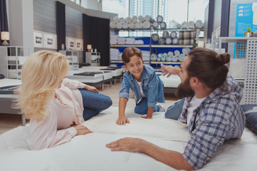 Healthy comfortable sleep concept. Happy family trying new orthopedica mattress together at furnishings store. Mature couple and their lovely son buying furniture for their home