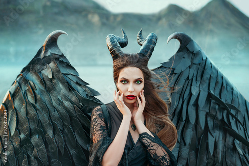 charming portrait of dark angel with sharp horns and claws on strong powerful wings, wicked witch in black lace dress brought hands to face, bright red lipstick and green eyes, art photo in blue shade