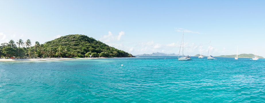 Tropical ocean and beach with sail boat yacht in the Tobago Cays, Saint Vincent and the Grenadines, Caribbean.