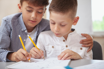 Family, children, brothers concept. Cropped shot of two cute young boys looking focused, drawing...