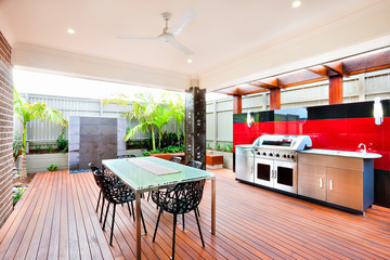Outside patio area with a roof and wooden pillars around tables and chairs next to the gas grill cabinet