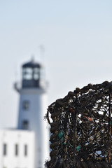 lobster pots in front of lighthouse