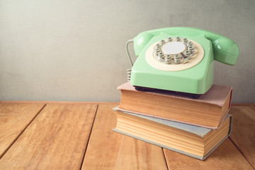 Retro telephone and old books on wooden table