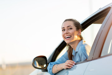 Happy woman driving a car and smiling Fototapete