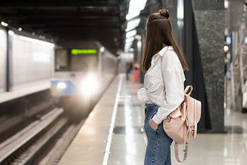 young european girl in jeans and shirt with backpack is waiting for the train at the metro station. Background in motion blur to convey a vibrant atmosphere. This is a snapshot idea.