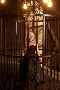 A beautiful, sexy young woman in a black evening dress, sits in a forged cage. A rich prisoner in prison.