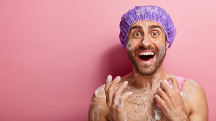 People, hygiene and pampering concept. Overjoyed man has shower, applies gel on skin with sponge, has foam on body, washes in bathroom, isolated on pink background, blank copy space for your advert