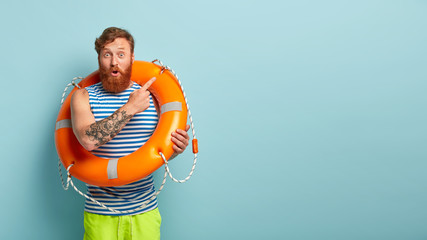 Surprised red haired man points aside away, poses with safety equipment, points aside on blank space, has tattoo on arm, shows direction somewhere, has astonished facial expression. Beach vacation