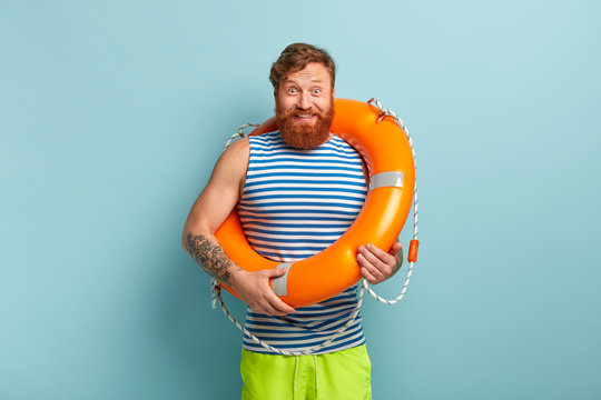 Happy carefree male with life preserver, has glad reaction, grins at camera, stands in casual clothes, isolated over blue backgound. Cheerful foxy sailor with swimming equipment. Safety concept