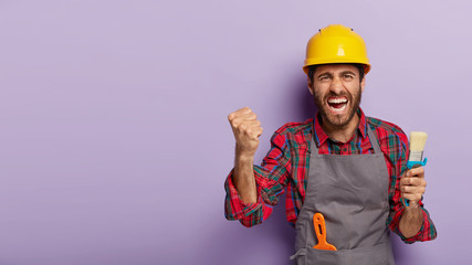 Annoyed handyman wears yellow hardhat and apron, holds paint brush, paints wall and does repairing in flat, isolated over purple background, clenches fist with irritation. Painter man at work
