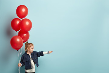 Horizontal shot of glad foxy girl in stylish clothes, points into distnace, celebrates birthday, holds red air balloons, has charming smile on face, isolated on blue studio wall. Children concept