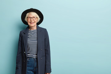 Active joyful stylish female teacher retires, wears hat and formal jacket, glad receiving congratulation from colleagues, has charming smile on face, isolated on blue wall, copy space area for advert Wall mural