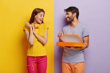 Happy young male model opens box, makes surprise for girlfriend on birthday, shows something in package, isolated over purple background. Glad lovely woman with headphones on neck, receives gift Wall mural