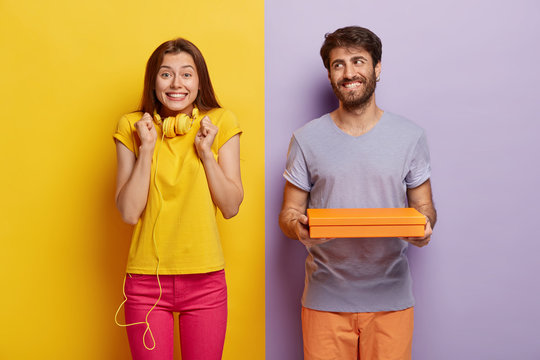 Glad female clenches fists, wears headphones on neck, waits for present from boyfriend, happy man holds small gift box, makes surprise for woman. Couple pose against two colored studio wall.