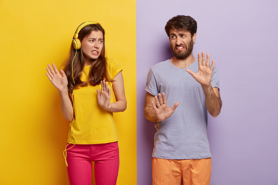 Displeased girlfriend and boyfriend make refusal gesture, feel aversion, smirk faces, dont like music, dressed in casual colorful clothes, isolated over yellow and purple background. Negative emotions