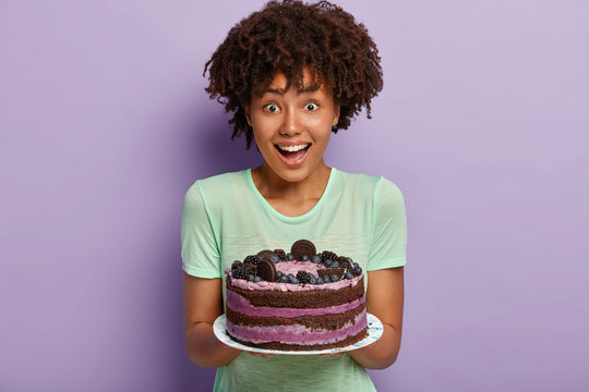 Half legth shot of female sweettooth with Afro hair, holds delicious sweet cake on plate, suggests guests taste dessert baked by herself, smiles positively, models over purple wall. Eating concept