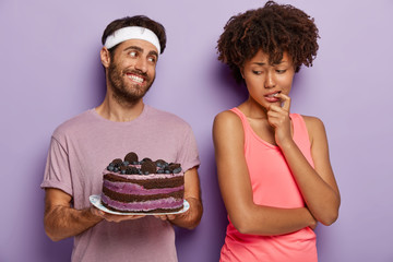 African American woman keeps finger on mouth, feels temptation while looks at delicious blueberry cake, tries not to eat unhealthy food, being on diet and goes in for sport. Mmm, how tasty it looks