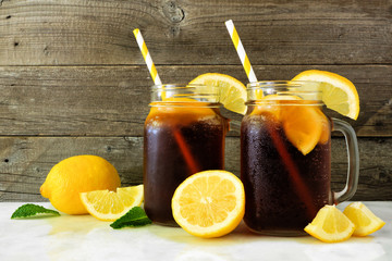 Iced tea in mason jar glasses with lemons. Side view on a rustic dark wood background.