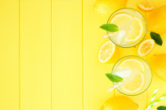 Sweet summer lemonade. Top view side border with copy space on bright yellow wood background.