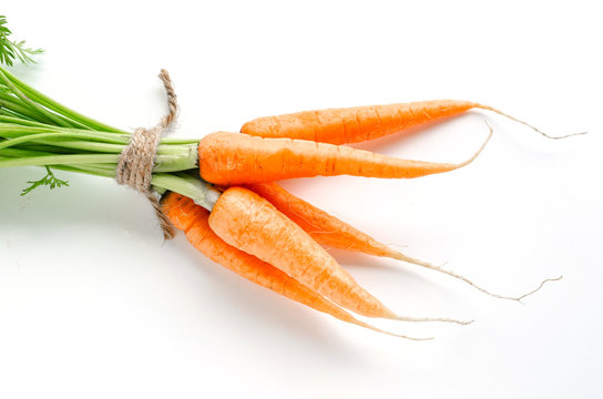 Fresh carrots with green foliage on white background.