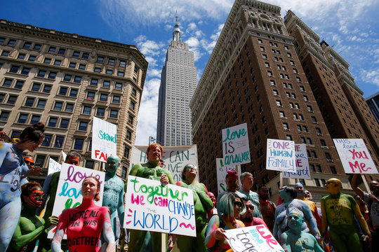 Protesters pose for a picture with the Empire State Building in the background as they march down Broadway during a protest against divisiveness organized by Human Connection Arts in New York