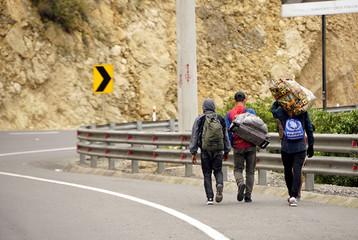 Venezuelans carry their belongings as they try to reach Peru in Tulcan