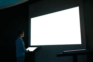 Woman using electronic kiosk and looking at white blank large interactive wall display in dark room of modern technology exhibition. Mock up, futuristic, template, education and technology concept Wall mural