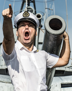 A navy officer standing beside gun and pointing his finger ahead.The captain issues an order to attack and shoot from a ship's cannon.