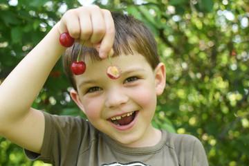 Happy boy eat organic natural healthy cherries in garden. Smiling little boy picks a cherry from a tree in cherry garden