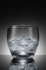 Water with ice cubes in a transparent glass on the background of a round gradient. Black and white image.