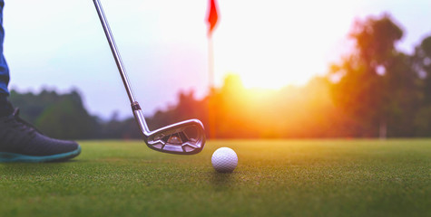 Golf balls and golf club on green grass shiny light sunse