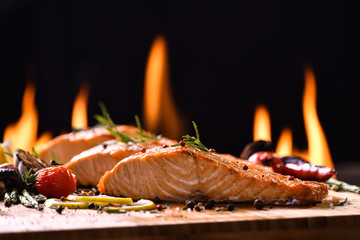 Fototapete - Grilled salmon fish and various vegetables on wooden table background