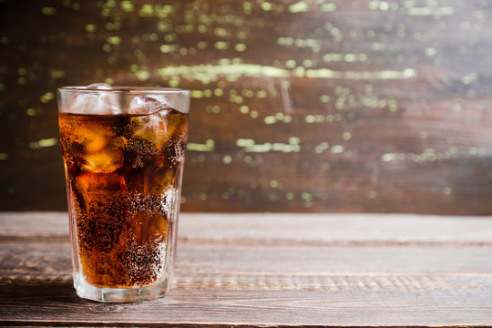 Refreshing cold cherry cola on the wooden background. Selective focus.