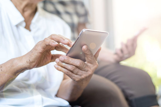 Happy elderly senior people society lifestyle technology concept. Ageing Asia women using tablet smartphone or mobile phone share social media together in wellbeing county home.
