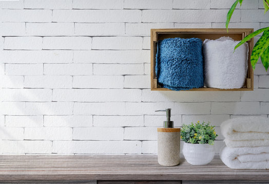 Clean towels with soap dispenser on shelf and wooden table in bathroom, white brick wall background.