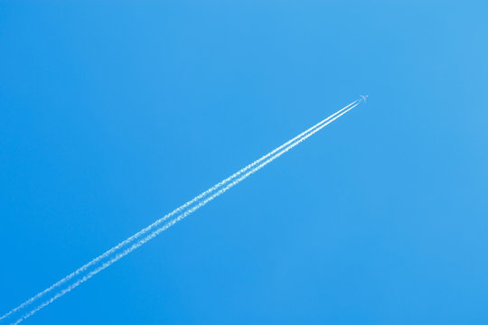 jet airplane flying at high altitude with contrails on beautiful blue sky, contrails or condensation trails or vapour trails, line-shaped clouds produced by aircraft engine exhaust