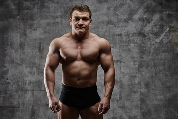 Sexy bodybuilder man posing on dark background in black shorts. Handsome pumped male body isolated with free space for advertising