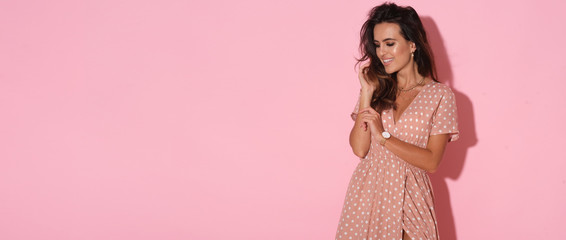 Lovely young adult woman in pink dress.