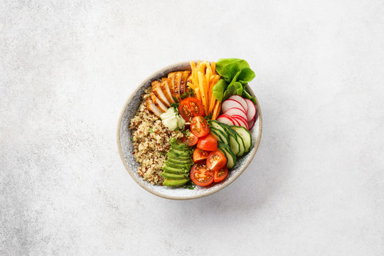 Healthy buddha bowl with chicken, quinoa and fresh vegetables.