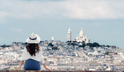 Wall Mural - Traveling in Europe, Young woman in white hat looking at Sacré-Cœur, famous landmark and travel destination in Paris, France in summer