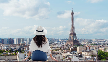 Wall Mural - Traveling in Europe, Young woman in white hat looking at Eiffel tower, famous landmark and travel destination in Paris, France in summer