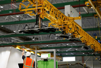 An employee directs an overhead crane used to move large parts around the facility during a media tour of the Boeing 777X at the Boeing Composite Wing Center in Everett