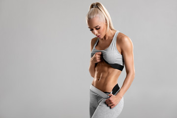 Fitness woman showing abs and flat belly, isolated on gray background. Beautiful athletic girl,...