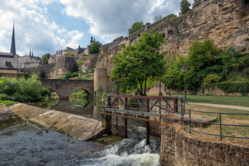 Weir Alzette river Luxembourg city with fortifications and stone bridge